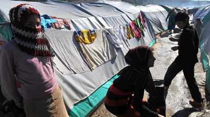 Syrian internally displaced people are seen outside a row of tents in the Bab al-Hawa camp along the Turkish border in the northwestern Syrian province of Idlib, on March 18, 2013.  (AFP Photo/Bulent Kilic)
