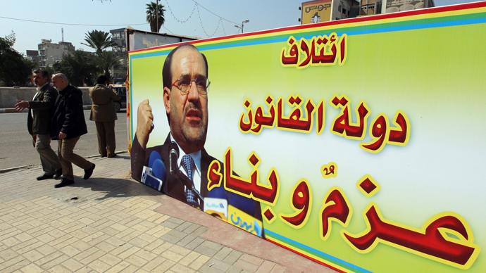 People walk past a campaign poster featuring Iraqi Prime Minister Nuri al-Maliki and announcing the provincial elections on March 2, 2013 near Tahrir Square in Baghdad (AFP Photo / Sabah Arar)
