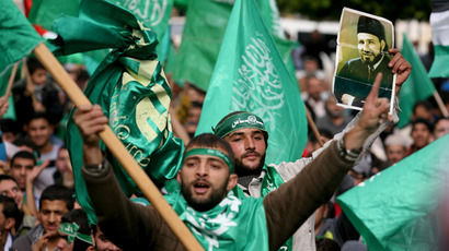 Hamas supporters carry a portrait of Muslim Brotherhood founder Sheikh Hassan al-Banna during a rally celebrating the 25th anniversary of the founding of Hamas Islamist mouvement on December 14, 2012 in the West Bank city of Tulkarem (AFP Photo / Saif Dahlah)