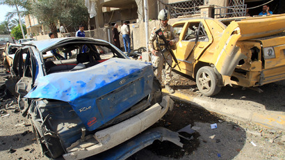 An Iraqi soldier looks at damaged cars at the site of a car bomb explosion near a Shiite islamic center in the Baghdad neighbourhoods of Qahira on March 29, 2013 (AFP Photo / Ali Al-Saadi)