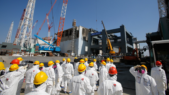 Members of the media wearing protective suits and masks being escorted by Tokyo Electric Power Co (TEPCO) employees as they visit near the No.4 reactor (C) and the construction of a foundation (R) for storage of melted fuel rods at TEPCO's tsunami-crippled Fukushima Dai-ichi nuclear power plant in the town of Okuma, Fukushima prefecture (AFP Photo / Pool / Issei Kato)