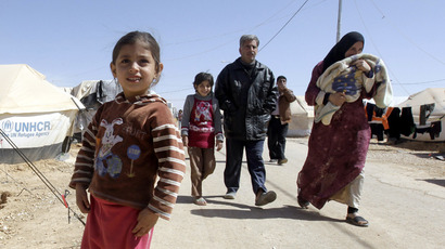 A Syrian family walk amid tents at the Zaatari refugee camp, near the Syrian border with Jordan in Mafraq (AFP Photo)