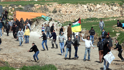 A Palestinian protestor waves his national flag amidst others throwing stones towards Israeli security forces during a demonstration against the closer of the main southwest entrance of the West Bank city of Hebron, which is situated near the Jewish settlement of Beit Hagai, in the occupied West Bank, on February 15, 2013.  (AFP Photo)