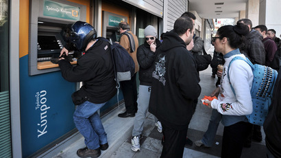 People withdraw money from Bank of Cyprus ATM's while employees gather outside the bank's headquarters in Athens (AFP Photo / Louisa Goulouimaki)