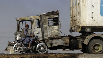 A motorcyclist rides past a smouldering NATO supply truck in the outskirts of Quetta (AFP Photo / Banaras Khan)