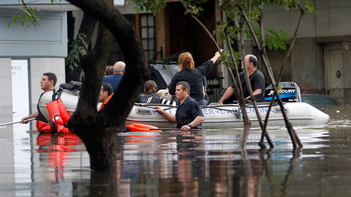 Residents are evacuated by rescue personnel in a flooded street after a rainstorm in Buenos Aires April 2, 2013.(Reuters / Enrique Marcarian)