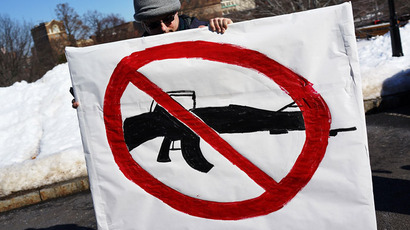 A man holds up a sign with with a depiction of an assault weapon during a rally at the Connecticut State Capital to promote gun control legislation.(Spencer Platt/Getty Images/AFP)