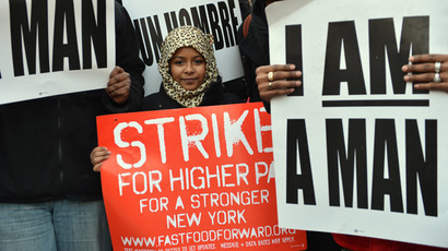 A girl holds a sign in Marcus Garvey Park in Harlem during a protest by fast food workers and supporters for higher wages April 4, 2013 in New York (AFP Photo / Stan Honda)