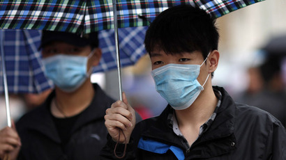 A man wears a face mask as he walks in a shopping area in downtown Shanghai April 5, 2013. (Reuters/Carlos Barria)