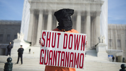 A protestor wears an orange prison jump suit and black hood on their head during protests against holding detainees at the military prison in Guantanamo Bay during a demonstration in front of the US Supreme Court in Washington, DC, on January 8, 2013. (AFP Photo/Saul Loeb)