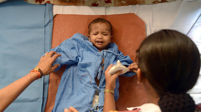 An unidentified child around ten months old, that survived a building collapse, recovers at a hospital in Thane, on the outskirts of Mumbai on April 5, 2013. (AFP Photo / Punit Paranjpe)