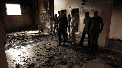 People inspect the inside of a the destroyed room in a building that was burnt down during a night of sectarian clashes between Christians and Muslims in Al-Khusus, a poor area in Qalyubia governorate, north of Cairo on April 6, 2013.(AFP Photo / STR)