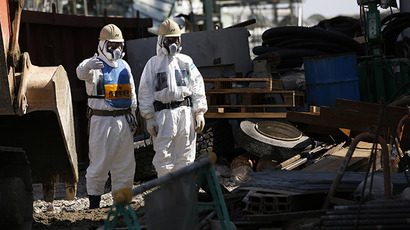 Workers wearing protective suits and masks are seen next to the No.4 reactor at Tokyo Electric Power Co's (TEPCO) tsunami-crippled Fukushima Daiichi nuclear power plant in the town of Okuma, Fukushima prefecture on March 6, 2013. (AFP Photo / Issei Kato)