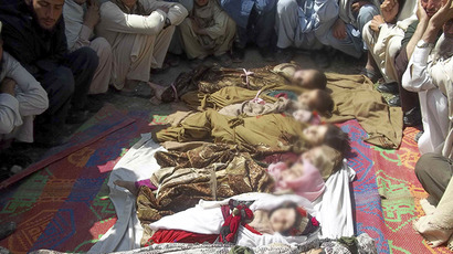 Afghan villagers sit near the bodies of children who they said  were killed during an air strike in Kunar province April 7, 2013. (Reuters)