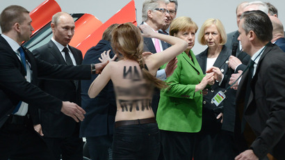 A topless dAemonstrator with a message on her back walks towards Russian President Vladimir Putin (L) and German Chancellor Angela Merkel (C) during their visit of the Hanover industrial Fair in Hanover, central Germany, on April 8, 213.  (AFP Photo/Jochen Lübke)