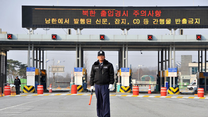 A South Korean security guard stands on the road leading to North Korea's Kaesong joint industrial complex, in front of the closed gate of the inter-Korean transit office in the border city of Paju on April 8, 2013 (AFP Photo / Jung Yeon-Je)