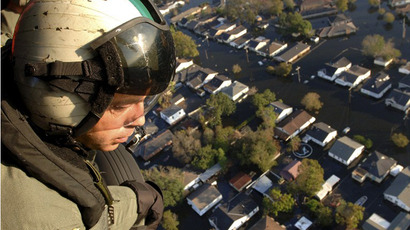 Navy Chief Aviation Warfare Systems Operator Scott Pierceas he looks out from the cabin of an SH-60 Seahawk helicopter at the flooded New Orleans streets caused by Hurricane Katrina on 07 September, 2005 in New Orleans, Louisiana. (AFP Photo)