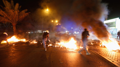 Riot police officers remove burning tires from a highway set up by anti-government protesters in the village of Diraz west of Manama April 11, 2013 (Reuters / Hamad I Mohammed)