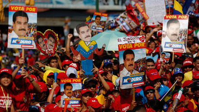 Supporters of Venezuela's acting President and presidential candidate Nicolas Maduro hold up placards and a cardboard figure of Maduro during his closing campaign rally in Caracas April 11, 2013 (Reuters / Tomas Bravo)