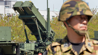 A soldier (R) of Japan's Ground Self Defence Force looks on as Japanese Foreign Minister Fumio Kishida (unseen in this picture) inspected Patriot Advanced Capability-3 (PAC-3) missile launchers at the Defence Ministry headquarters in Tokyo on April 13, 2013 (AFP Photo / Yoshikazu Tsuno)