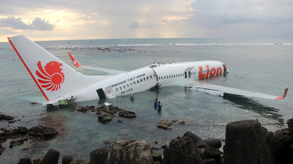 This handout photo released by the Indonesian Police on April 13, 2013 shows a Lion Air Boeing 737 submerged in the water after skidding off the runaway during landing at Bali's international airport near Denpasar (AFP Photo / Indonesian Police)