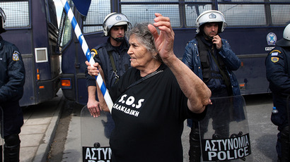 A woman holding a Greek flag shouts slogans as police blocks the road to the police station of Thessaloniki. (AFP Photo / Sakis Mitrolidis)