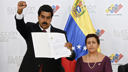 Venezuelan President elect Nicolas Maduro (L) raises his fist as he shows a document delivered by the president of the national electoral council, Tibisay Lucena, in Caracas on April 15, 2013 (AFP Photo / Juan Barreto)