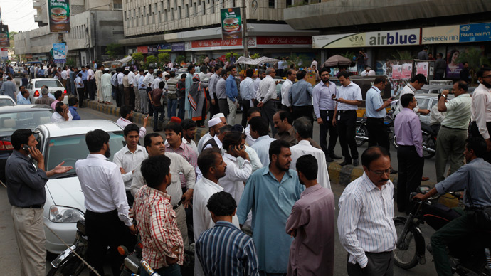 People stand outside of their office buildings following an earthquake tremor in Karachi April 16, 2013 (Reuters / Athar Hussain)