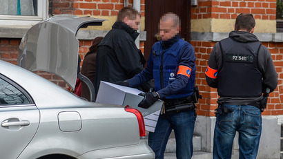 Police officers load the trunk of a car with evidence seized during a search on April 16, 2013 at a house in the Vilvoorde station area (AFP Photo / Belga)