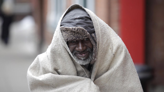 A homeless man covers himself from the cold while walking down a sidewalk February 24, 2013 in Detroit, Michigan.  (J.D. Pooley/Getty Images/AFP)