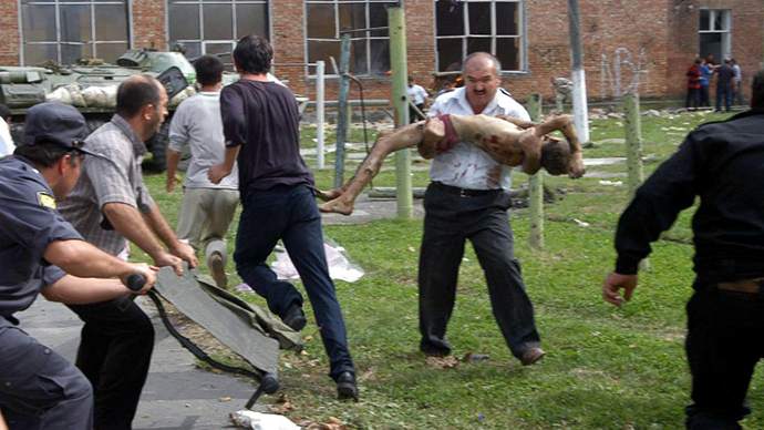 A volunteer carries an injured schoolboy in the school garden during the rescue operation in Beslan, northern Ossetia, 03 September 2004. (AFP Photo / Yuri Titov)