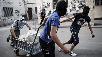 Bahraini protesters use a trolley to carry bricks during clashes with riot police following a protest against the Formula One Grand Prix on April 19, 2013.(AFP Photo / Mohammed Al-Shaikh)