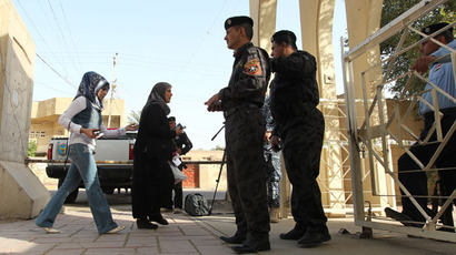 raqi security forces keep watch as people arrive to cast their votes during provincial elections on April 20, 2013 in Baghdad.(AFP Photo / Sabah Arar)