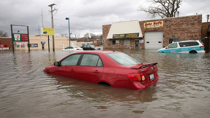 A car is stranded in the middle of a downtown street after being overcome by floodwater April 19, 2013 in Des Plaines.(AFP Photo / Scott Olson). YouTube video courtesy / fastrains56