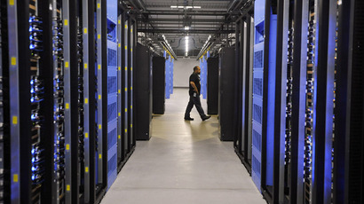 An employee walks past servers in one of four server rooms at the Facebook Data Center on April 19, 2012 in Forest City, North Carolina. (AFP Photo)