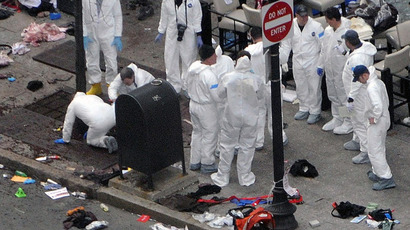 Investigators in white jumpsuits work the crime scene on Boylston Street following bomb attack at the Boston Marathon April 16, 2013 in Boston, Massachusetts.  (Darren McCollester/Getty Images/AFP)
