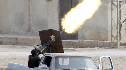 A Free Syrian Army fighter fires an anti-aircraft artillery weapon during an air strike in the Syrian town of Ras al-Ain (Reuters / Osman Orsal)