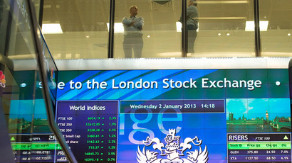 Workers speak above an electronic information board at the London Stock Exchange in the City of London (Reuters/Paul Hackett)