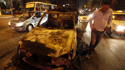 A man walks near a burnt police car set on fire by protesters opposing Egyptian President Mohamed Mursi during clashes that broke out with riot police during a rally in support of the judiciary, in front of El-Thadiya presidential palace in Cairo April 26, 2013. (Reuters / Amr Dalsh)