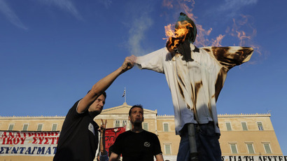 Protesters burn an effigy depicting a Greek worker during a rally against the government's plan to fire thousands of public sector workers as part of its austerity reform program, in Athens April 28, 2013. (Reuters/John Kolesidis)