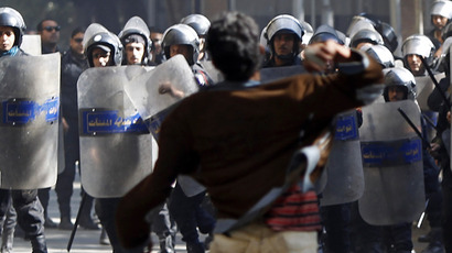A protester opposing Egyptian President Mohamed Mursi throws a stone at riot policemen during the funeral of activists Mohamed al-Gendy and Amr Saad in Cairo February 4, 2013 (Reuters / Amr Abdallah Dalsh)