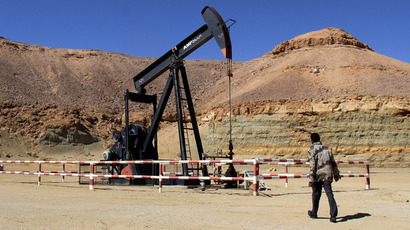 A libyan security member walks by an oil drill on March 23, 2013 at the al-Ghani oil field, belonging to Libya's Harouge Oil Operations company, near the city of Waddan in the central Al-Jufrah province.  (AFP Photo)