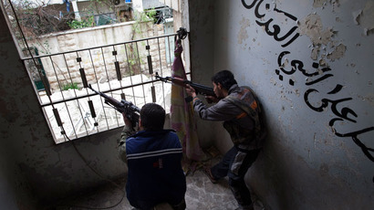 Syrian rebels aim their weapons as they take position in a building during clashes with regime forces in the Salaheddine district of Aleppo in northern Syria on March 16, 2013.(AFP Photo / Jm Lopez)