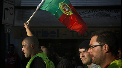 A worker holds the Portuguese flag during a protest against government austerity measures. (AFP Photo / Patricia De Melo Moreira)