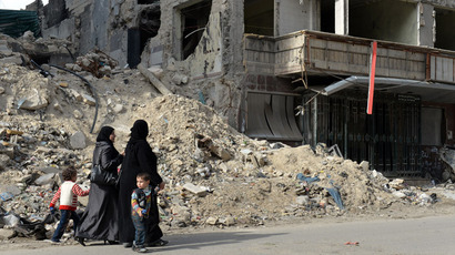 Syrian women walk past the destruction at Dar Al-Shifa hospital in the northern city of Aleppo on April 21, 2013. (AFP Photo)