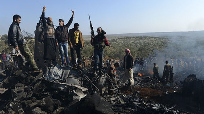 Syrian rebels celebrate on top of the remains of a Syrian government fighter jet which was shot down at Daret Ezza, on the border between the provinces of Idlib and Aleppo, on November 28, 2012.(AFP Photo / Francisco Leong)