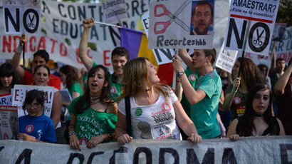 Students hold banners and placards as they take part with thousands of people in a protest against the government's cuts to education spending in Madrid, on May 9, 2013.(AFP Photo / Pedro Armetre)