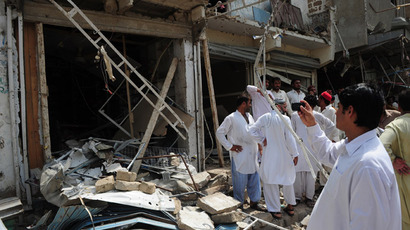 Pakistani residents gather at the site of a bomb explosion in Karachi on May 11, 2013. (AFP Photo; AP video shows the aftermath of the first blasts to hit Karachi on the election day)