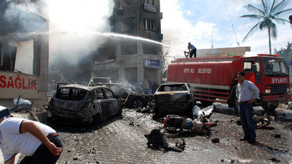 People stand on the site of a car bomb explosion on May 11, 2013 near the town hall of Reyhanli, just a few kilometres from the main border crossing into Syria, killing 18 people in one of the deadliest recent attacks in the volatile area. (AFP Photo/IHLAS NEWS AGENCY)