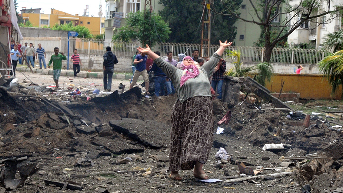 A woman raises her arms and shouts as she stands on the site where car bombs exploded on May 11, 2013 near the town hall in Reyhanli (AFP Photo / Cem Genco)